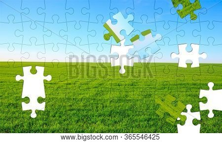 Assorted Jigsaw Puzzle Of An Empty Field With Green Grass And Blue Sky In The Background