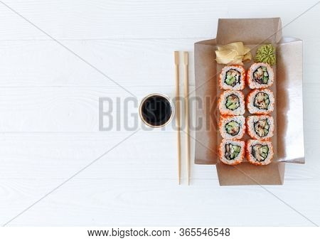 Take Away Japanese Sushi Rolls Set California On White Wooden Table. Asian Healthy Food To Go. Copy