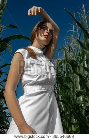 Portrait Of A Fair-haired Girl In Fashionable And Stylish Clothes, Among The Foliage Of A Corn Field