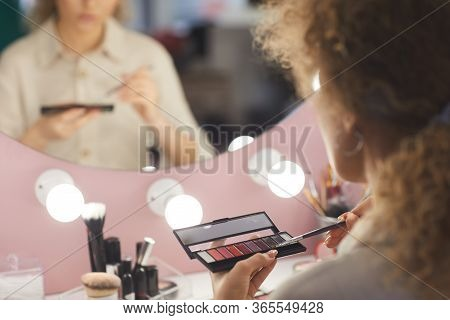 Back View Close Up Of Unrecognizable Young Woman Holding Eyeshadow Palette While Applying Make Up By