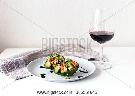 Healthy Vegan Lunch With Salad Into Avocado Bowl. Avocado, Tomato, Microgreens With Balsamic Sauce