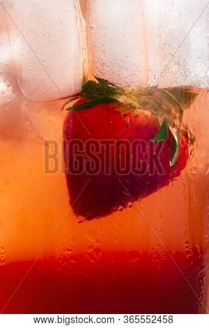 Strawberry Lemonade Close-up. Cold Summer Drink Macro Details With A Strawberry, Ice Cubes, And Red