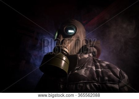 Gas Mask With Clouds Of Smoke On A Dark Background. Sign Of Radioactive Contamination. Means For Rad