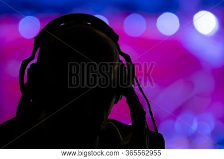The Dark Silhouette Of A Man In Headphones On The Background Of Multicolored Glare And Lights Of The