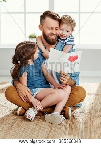 Cheerful Little Boy And Girl Congratulating Happy Dad With Fathers Day And Giving Handmade Greeting