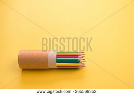 Color Pencils In Reusable Paper Tube Packaging On Yellow As Creative Background Or Mockup With Copys