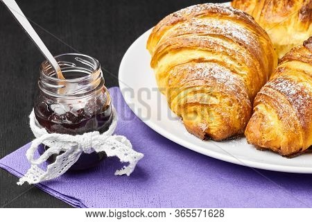 Close Up French Croissants, Jar Of Jam Served On A Purple Serviette. Homemade Baking From Puff Dough