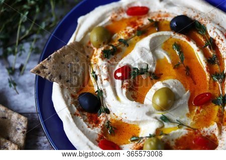 Hummus With Olives, Paprika And Olive Oil On A Plate. Blue Plate Serving Hummus.