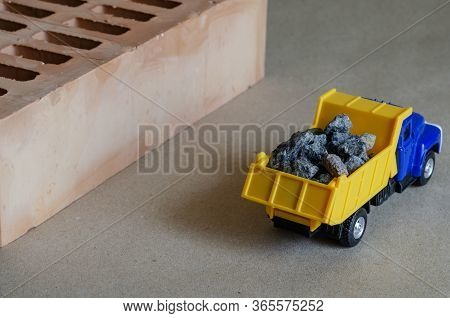 A Yellow Dump Truck Carries Rubble Next To A Brick. Toy Truck With A Full Body Of Building Materials