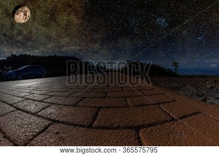 Starry Night Sky Over A Mountain Road, In The Silver Light Of A Huge Bright Moon. Lonely Pine On A S
