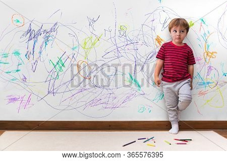 Child Mischief. Boy With A Distracted Face Because He Drew The Entire Wall. Little Boy Leaning Again