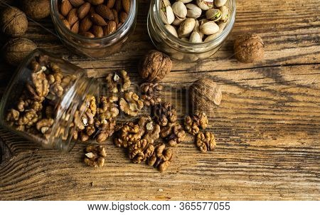 Walnut Scattered On The Vintage Table From A Jar Whith A Whole Walnuts. Walnut Is A Healthy Vegetari