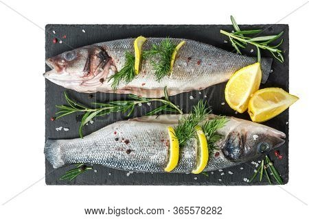 Fresh Fish Seabass And Ingredients For Cooking. Raw Gutted Fish Seabass With Spices And Herbs On Bla