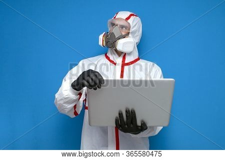 Disinfection Worker In Protective Suit And Respirator Checks Coronavirus Statistics On Laptop, Virol