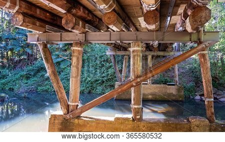 Underneath A Sturdily Built Timber And Steel Bridge Over A Creek In A Rainforest