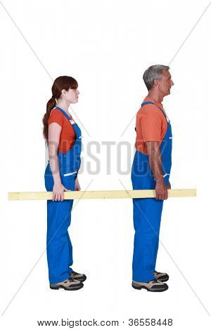 Man and woman carrying a plank of wood