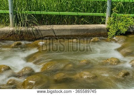 Water Flowing Rapidly Over Stones In Shallow Waterway.