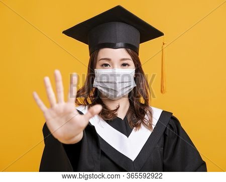Young Woman In Graduation Gowns With Medical Mask  And Showing Stop Gesture