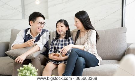 Happy Asian Family Watching Tv Together Spending Time In Quarantine On Sofa In Living Room. Family A