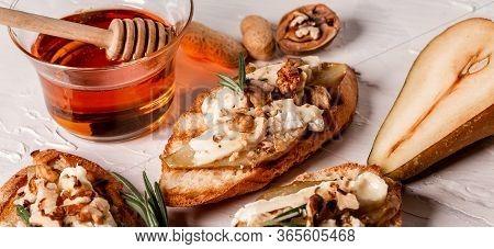 Close Up Pear And Nuts Brie Crostini. Long Banner Format Menu Recipe