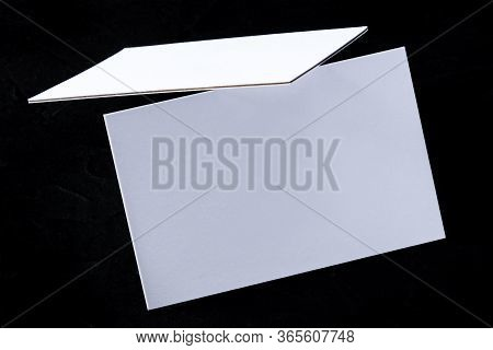 White 3-ply Business Cards, Floating On A Black Background, A Mock-up
