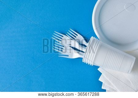 Disposable Plastic Tableware, Forks, Glasses, Plates On A Blue Background. The Problem Is Recycling,