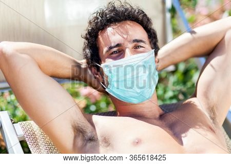 Young Man Sunbathing By Pool wearing a mask, coronavirus concept