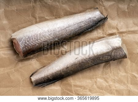Two Frozen Hake, Headless And Tailless Fish, On Rough Brown Crumpled Paper.