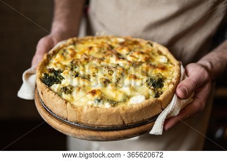 Male Hands Holding Cheese And Broccoli Quiche Tart. Home Cooking According To French Recipe.