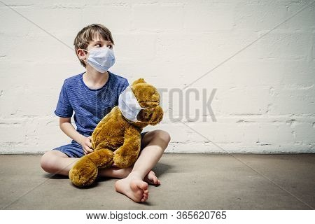Young Boy Wearing A Mask Holding His Teddy Bear During Covid-19 Pandemic.