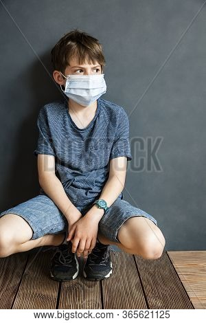 Young Boy Sitting Against A Wall Wearing A Protective Mask During Covid-19 Pandemic.