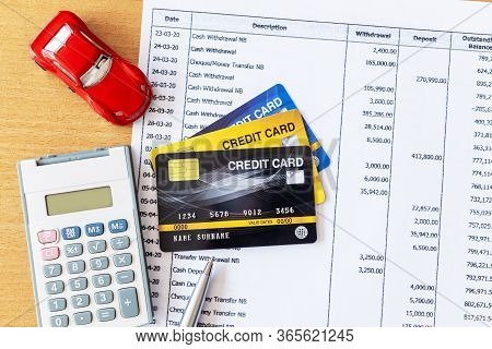 Car Model And Calculator On Bank Statement And Credit Card On A Wooden Table.