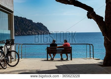 Sant Elm, Mallorca, Spain - April 12, 2019: 2 Man Sitting On A Wodden Bench Under A Big Tree With Vi