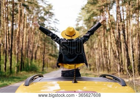 Girl Standing Out Of Yellow Car Sunroof Back View. Free Woman Raise Up Arms Wearing Leather Jacket A