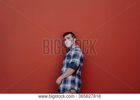 A Masked Man Is Leaning Against A Red Wall