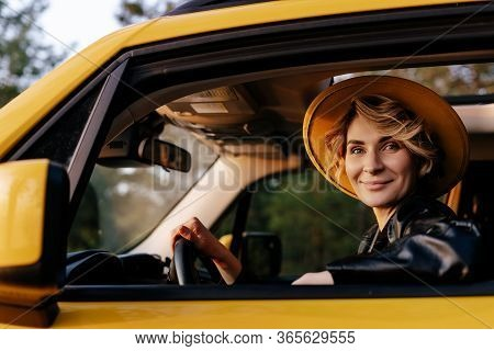 Beautiful Young Woman Driving Yellow Taxi Car. Happy Blonde Female Smile In Hat Looking At Camera. C