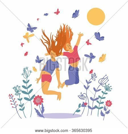 Two Teenage Girls Jump On The Grass Among Flowers. Butterflies Flutter Around The Girls. Funny Child