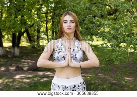 Woman Does Yoga In The Park, Woman Holds Her Hands On The Namaste Yoga