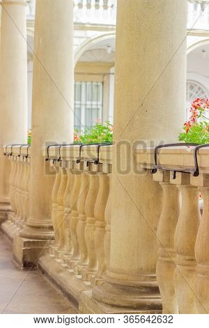 Fragment Of The Stone Balustrade With Balusters And Columns, Decorated With Flowers In Gallery Of An