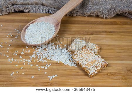 White Sesame Seeds In The Wooden Spoon And Scattered Beside On The Wooden Surface, Sesame Cookies Cl