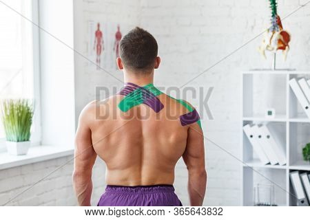 Kinesiology Taping. Kinesiology Tape On Patient Neck. Injured Trapezius Muscles Treatment Of Young M