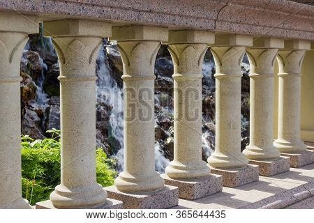 Stone Balusters In Balustrade On Footbridge On A Blurred Background Of Small Waterfall In Park, Frag