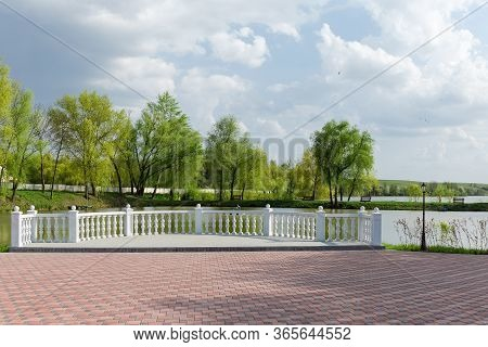 Observation Deck With White Balustrade Over Pond And Area Paved With A Tile On A Foreground In The P