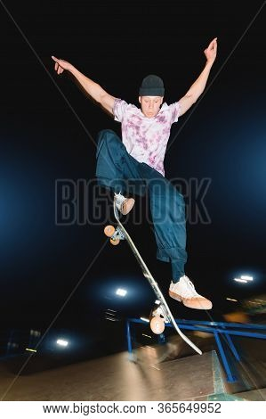 A Young Skatecrack In A Night Skatepark Does A Halfpipe Jump Jump. Youth Culture Leisure Concept At