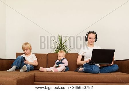 Nanny With Laptop To Surf Internet While Kids Play With Phones. Bad Nanny Concept.