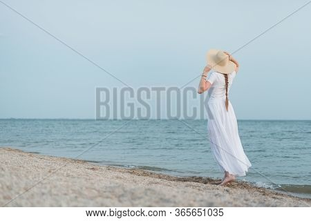 Rear View Of Young Woman In White Dress Walking On Beach Along Sea.
