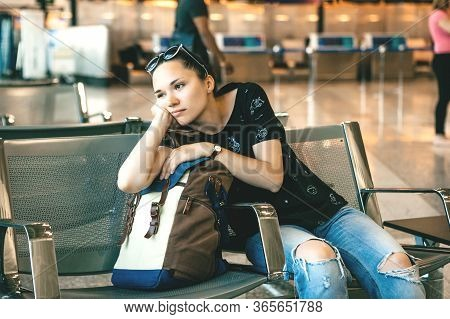 Upset Or Bored Girl Tourist Or Student At The Airport. Her Flight Was Delayed Or She Was Tired.