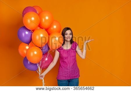 Doubtful Puzzled Woman In Pink T-shirt Posing With Bright Colorful Air Balloons Isolated On Orange B