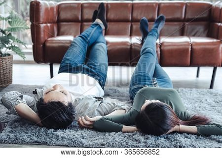 Young Couple Having Relaxing While Lying On Carpet At Their Home, Attractive Asian Couple Love Are R