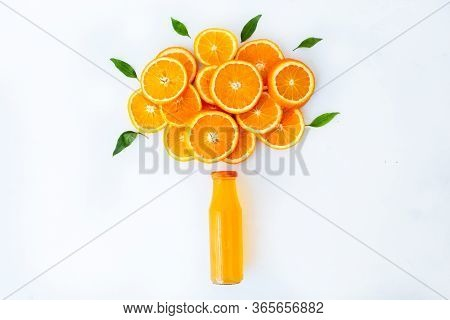 Fresh Orange Juice With Oranges And Orange Slices And Leafmon White Table